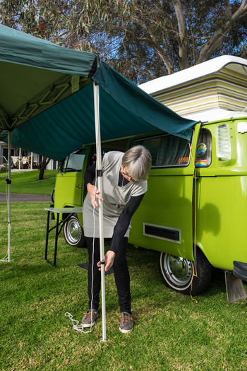 Retired couple setting up canopy tent Australia Cam Camping Canopy Day Grass Grey Nomads Leisure Activity One Person Preparation  Real People Retirement Seniors Set-up Setting Up Tent Travel Destinations