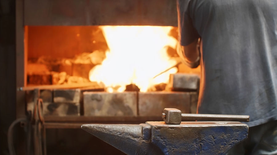 Midsection of man standing by fire in workshop