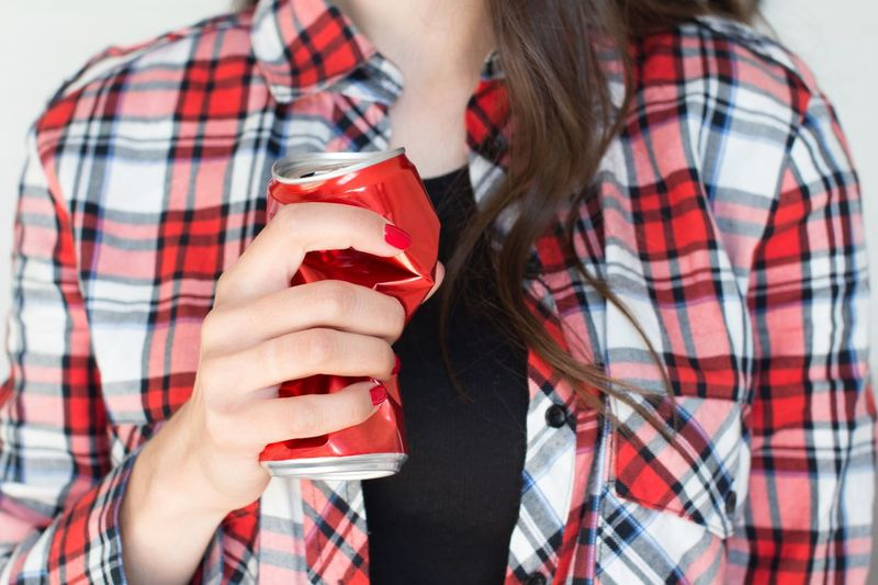 Young woman with long hair in plaid red shirt holding and squeezing red soda can Thirst Beer Can Party Addiction Aggression  Bad Habit Alcoholic  Alluminum Can Soda Water Social Issues Garbage Drink Can Alcohol Abuse Anger Beer - Alcohol Sugar Emotional Stress Alcohol Free Recycling Modern Art Sobriety  Drunk Pollution Holding Young Adult Midsection Checked Pattern Lifestyles Refreshment Drink