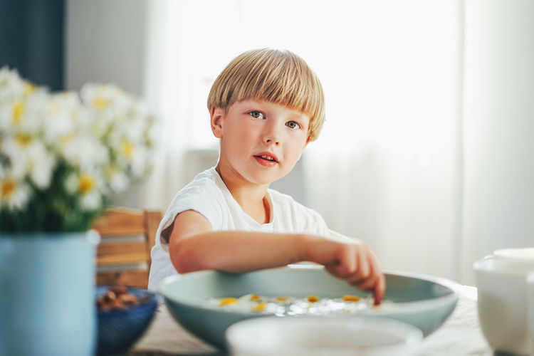 Portrait of boy sitting by table at home