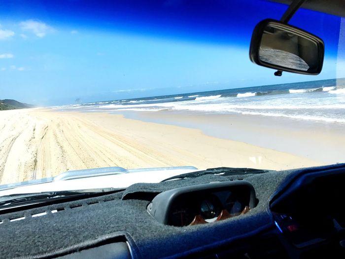 Car on beach against sky