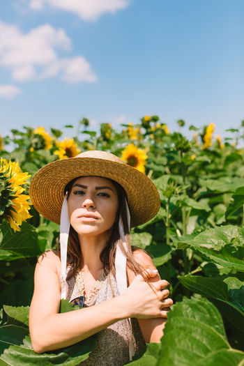 Woman with a straw straw hat standing in the sunflower field