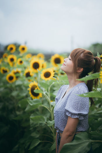 Midsection of woman standing on sunflower