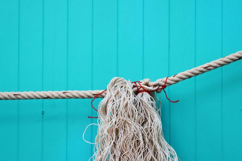 Close-up of rope tied against turquoise wall