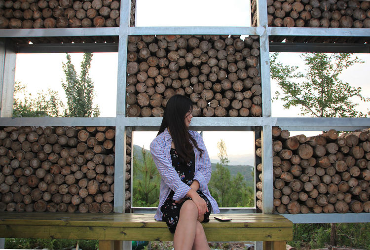 Woman sitting on bench against stacked logs