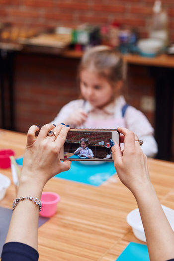 Mother photographing girl in baking workshop on smart phone
