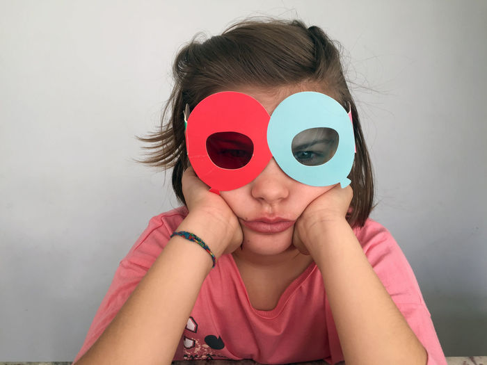 Portrait of woman wearing 3-d glasses against wall