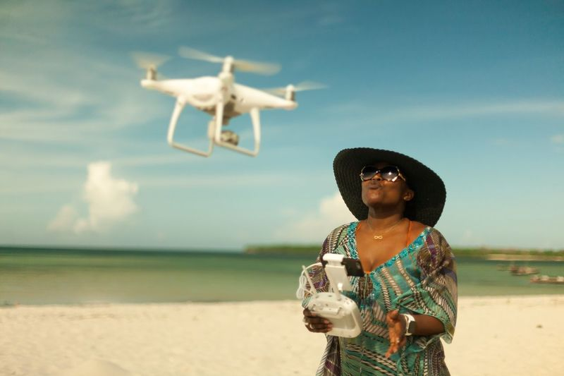 Mid adult woman flying drone at beach