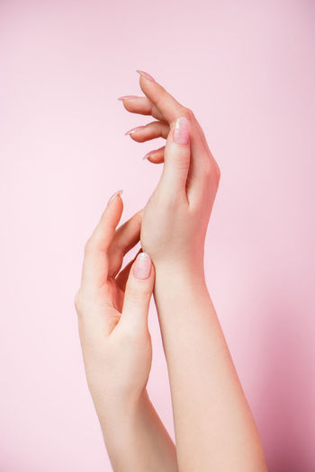 Close-up of woman hand against pink background