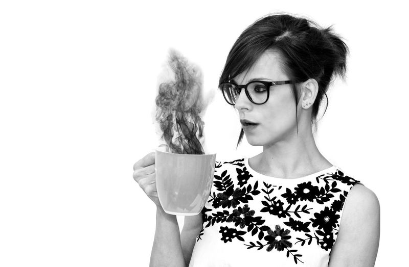 Portrait of woman wearing eyeglasses against white background