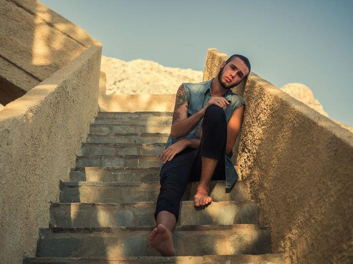 Full Length Portrait Of Man Relaxing On Steps