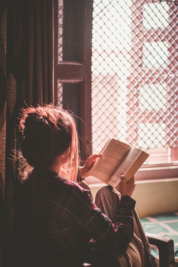 Woman reading book while sitting on bed by window