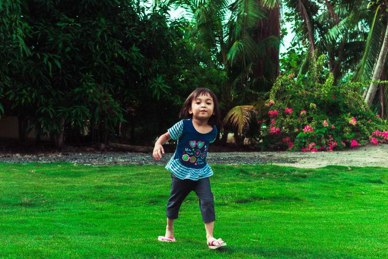 Full length portrait of girl on grass against trees