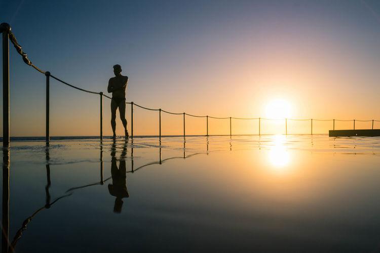 Shirtless man walking by railing in infinity pool during sunset