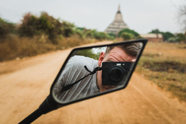 Reflection of man photographing with camera in side-view mirror of motorcycle on road