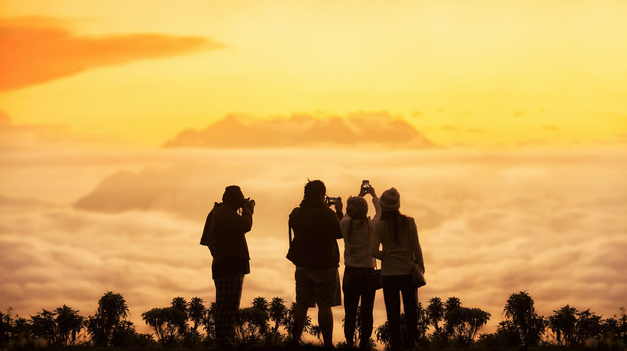 Rear View Of Friends Photographing Cloudscape During Sunset