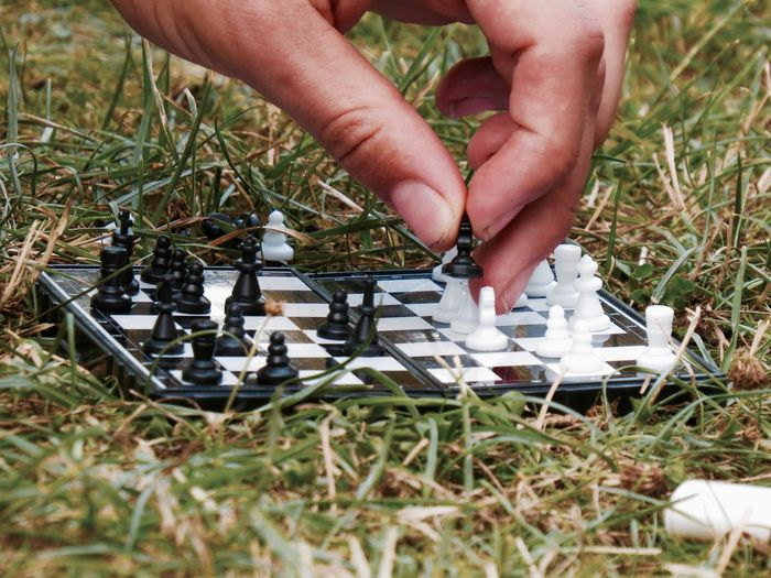 Cropped hand of person playing chess on grass