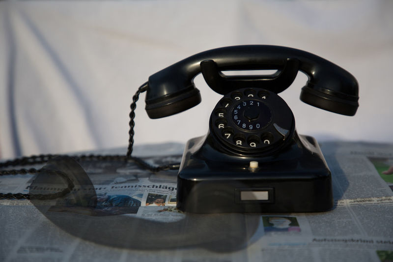 Double Exposure Of Old-Fashioned Rotary Phone On Table