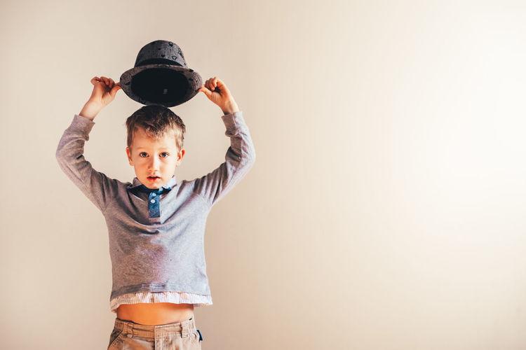 Portrait of cute boy standing against beige background