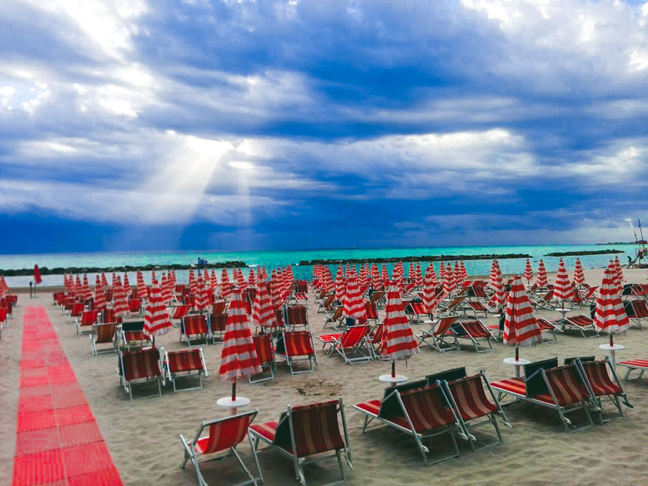 sky, chair, cloud - sky, seat, red, in a row, absence, nature, large group of objects, beach, land, water, no people, horizon, horizon over water, sea, arrangement, lounge chair, day, outdoors, order, outdoor chair