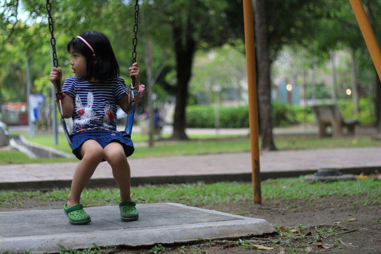Kid plays on a Swing Swing Playground Child Adult One Girl Only Nature Children Only Vacations Lifestyles Full Length Rear View Tree Young Adult Real People Leisure Activity