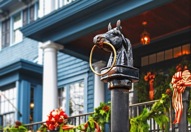 Horse hitching post in front of a country inn decorated for Christmas. Christmas Decoration Holiday Horse Hitching Post Porch Inn Architecture Outdoors Building Exterior Architectural Column Built Structure Travel Destinations No People Lantern