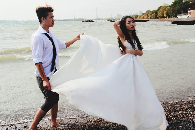Boyfriend holding girlfriend white dress while standing on shore at beach