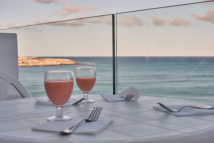Wine glass on table by sea against sky