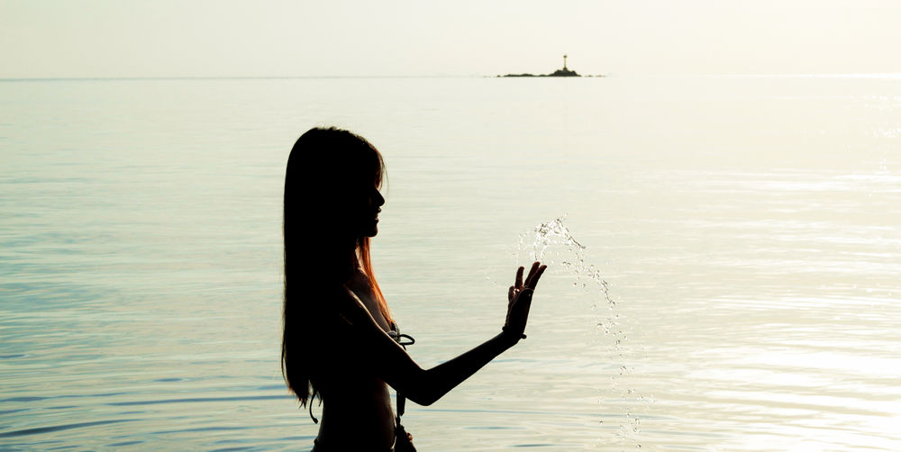 Silhouette of a woman in the sea NOMAD Silhouette Beauty In Nature Blue Dawn Day Evening Island Long Hair Mysterious Nature Nomadic Ocean One Person Outdoors People Real People Sea Sexygirl Sky Solitude Splash Splashing Sunset Water