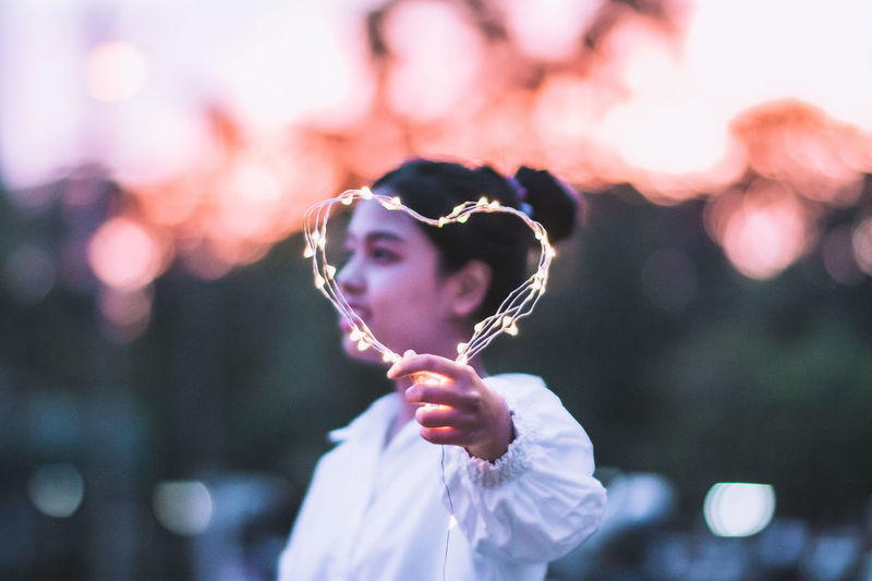 Side View Of Young Woman Holding String Light