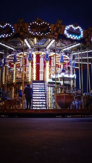 Side view of illuminated carousel at amusement park