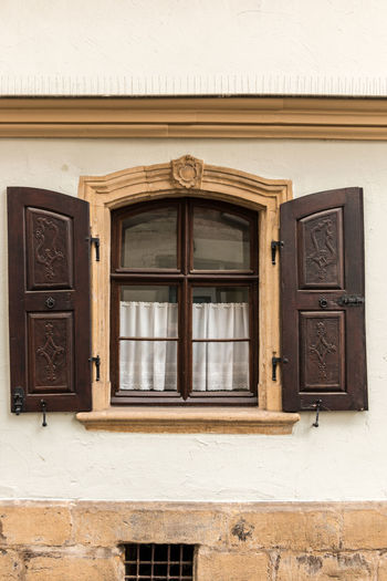 Old window made of stone and wood with brown shutters Window Architecture Building Exterior Built Structure Wood - Material No People Day Building Door Wall - Building Feature Entrance Brown Outdoors House Closed City Backgrounds Safety Façade Ornate