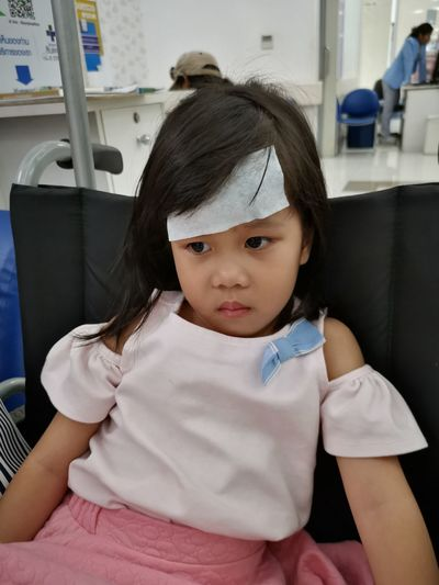 Close-up of girl with bandage on head sitting in hospital