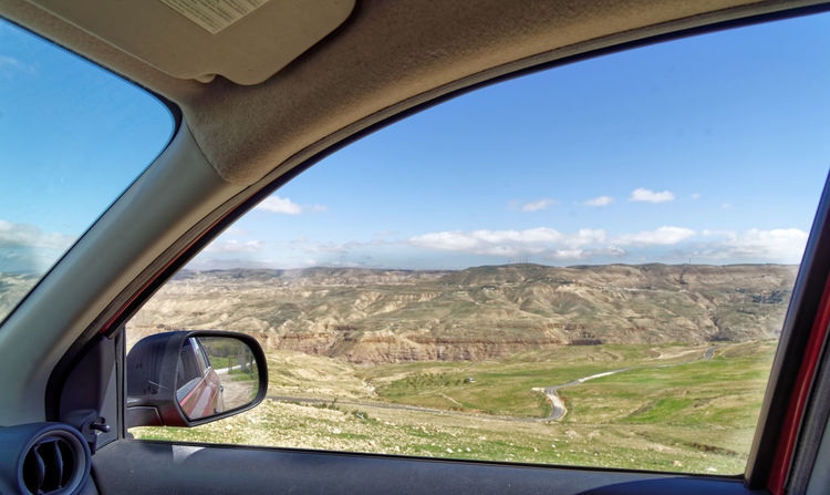 View through the window of a rental car to the edge of Dana Biosphere Reserve, Jordan, middle east Jordan Car Car Interior Car Rental Day Environment Glass - Material Land Land Vehicle Landscape Mode Of Transportation Motor Vehicle Mountain Nature No People Outdoors Road Scenics - Nature Sky Transparent Transportation Travel Vehicle Interior Vehicle Mirror Window Go Higher