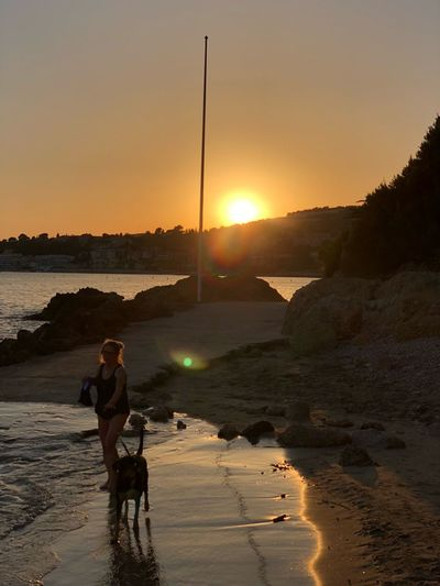 Woman with dog walking at beach during sunset