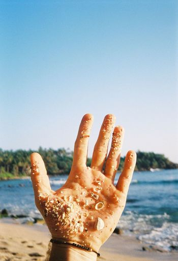 Close-up of hand holding sand on beach against clear sky