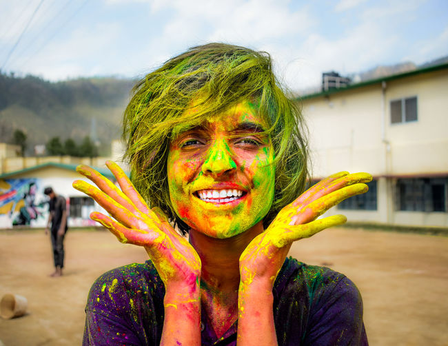Portrait of smiling woman with multi colored face powder
