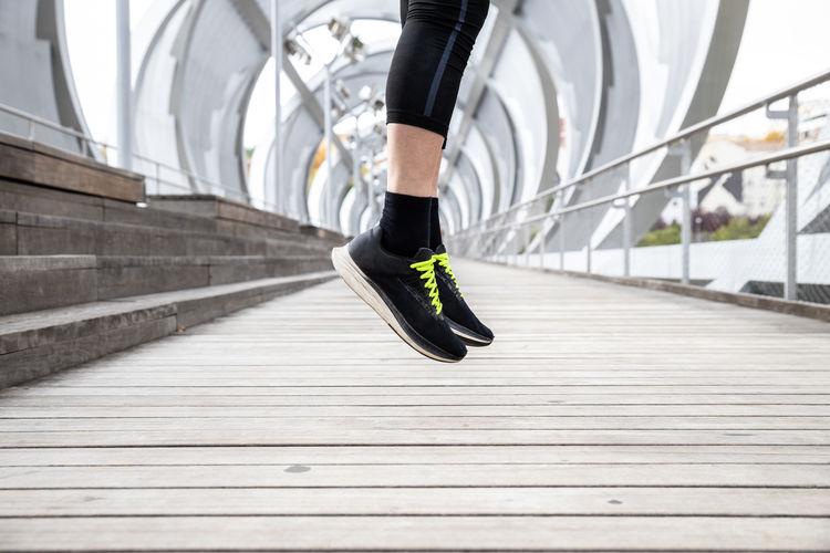 Low section of man running on footbridge