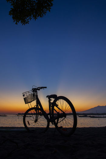 Silhouette bicycle at beach against sky during sunset