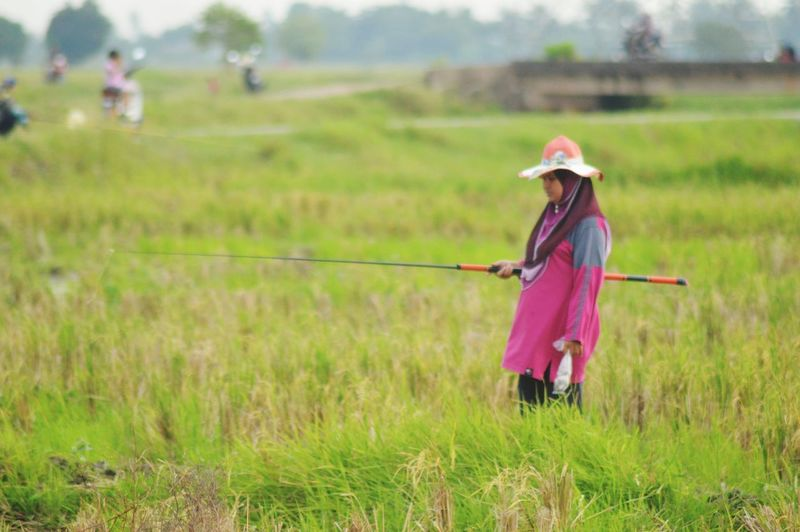 Memancing ikan puyu Freshwater Fishing Memancing Ikan Puyu Rural Scene Farmer Full Length Agriculture Women Asian Style Conical Hat Field Rice Paddy Grass Sky Agricultural Field Farmland