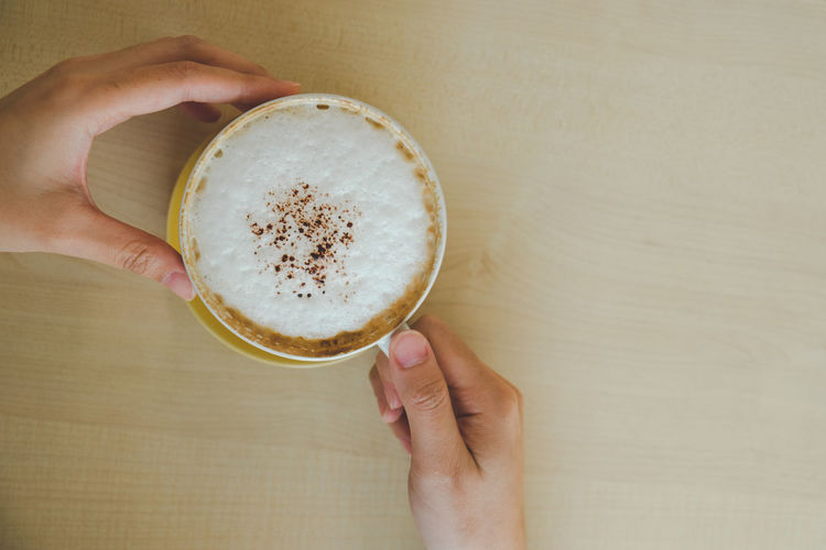Directly above shot of hand holding coffee cup on table
