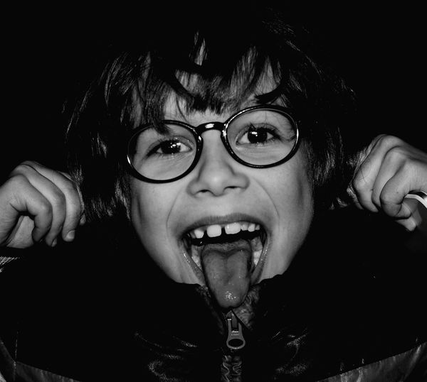 Close-up portrait of young boy sticking out tongue
