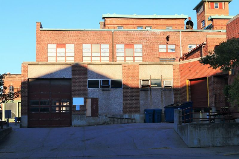 A loading dock at the back of a red brick industrial building Architecture Building Exterior Built Structure City Clear Sky Day Garage Door Industrial Building  Loading Dock No People Outdoors Red Brick Sky