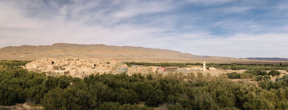 Panoramic view over the old village of Ghazouane near Talsint with some trees in the foreground and a small mountain in the background. The village is near Talsint, Morocco. Africa Architecture Beauty In Nature Building Exterior Built Structure Cloud - Sky Culture Day Ghazouane House Kasbah Landscape Moroccan Morocco Mountain Mountain Range Nature No People Outdoors Scenics Sky Talsint Tranquility Tree