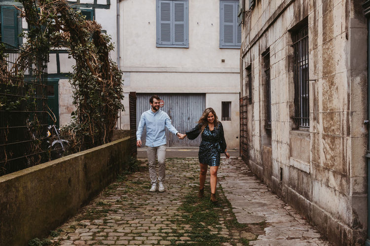 Full length of couple walking amidst buildings