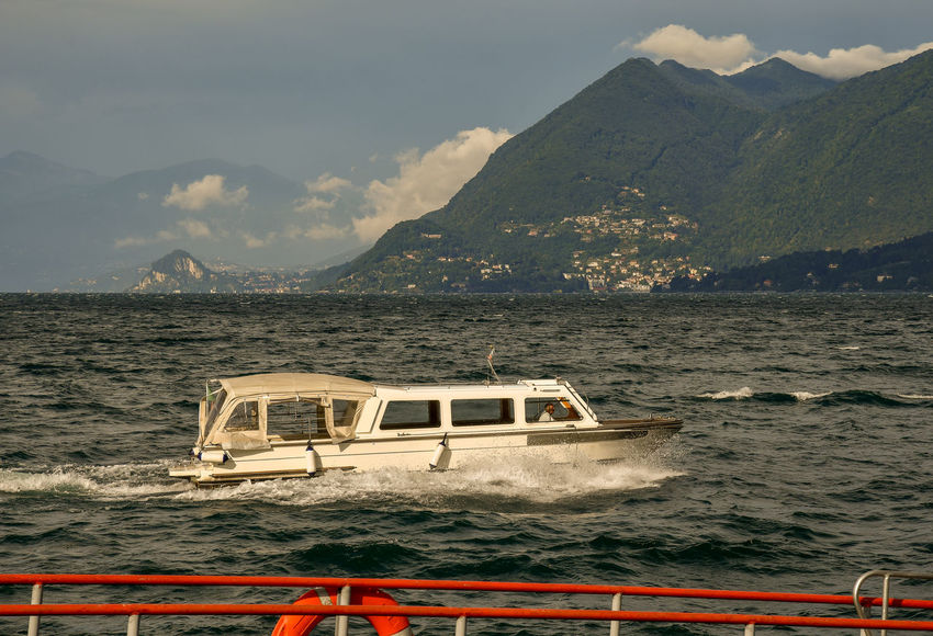 Boat in navigation on Maggiore Lake with mountainous coast in the background, Piedmont, Italy Mountain Water Nautical Vessel Transportation Mode Of Transportation Mountain Range Sky Beauty In Nature Scenics - Nature Nature Cloud - Sky Non-urban Scene Tranquil Scene Travel Tranquility Outdoors Lake Maggiore Lake Stresa Italy Coast Boat Scenic Waves Piedmont Italy Ship