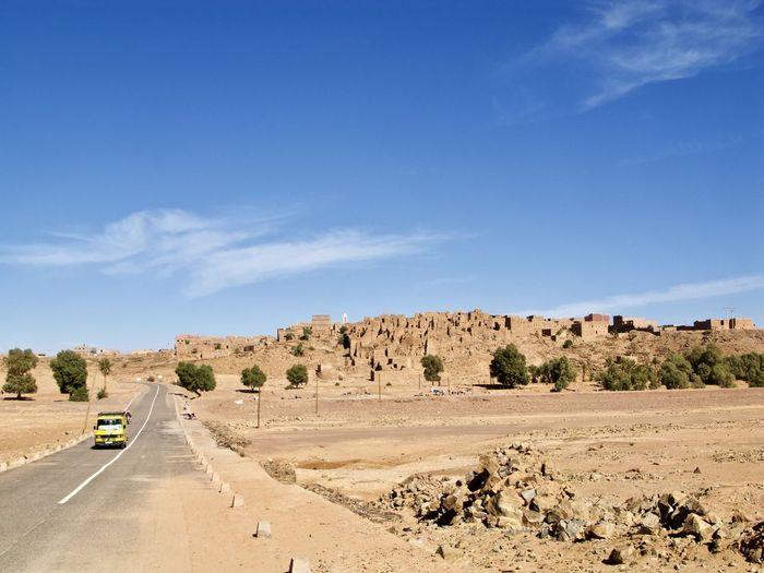 Scenic View Of Desert Road Against Blue Sky