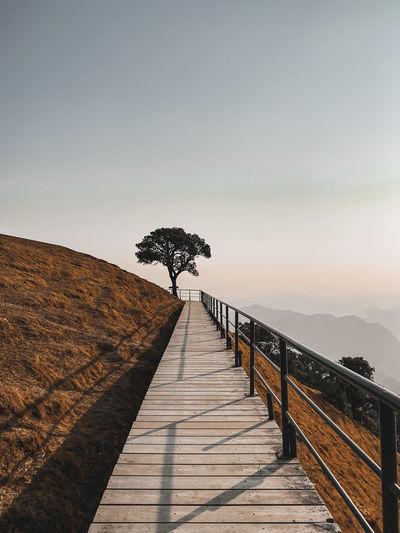 Footpath by railing against sky