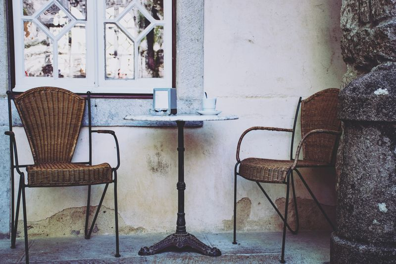 Empty chairs and table against wall in old building