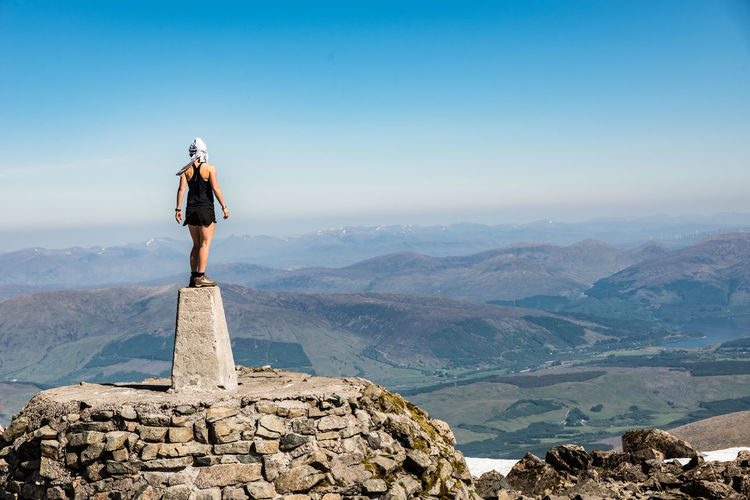 A middle aged female hiker on the top of ben nevis peak, fort william, scotland